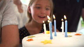Slow Motion Sequence Of Girl Blowing Out Candles On Cake Stock Photography