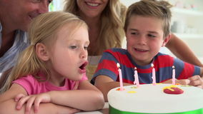 Slow Motion Sequence Of Girl Blowing Out Candles On Cake Stock Image