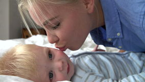 Slow Motion Sequence Of Mother And Baby Boy Playing In Bed stock footage