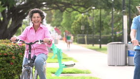 Slow Motion Sequence Of Senior Couple Riding Bikes In Park