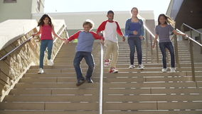 Slow Motion Sequence Of Teenagers Running Down Stairs. Group of teenage children running down steps in slow motion.Shot on Sony FS700 at frame rate of 50fps stock footage