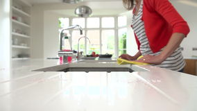 Slow Motion Sequence Of Woman Cleaning Surface In Kitchen stock video