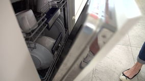 Slow Motion Sequence Of Woman Emptying Dishwasher stock video