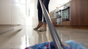 Slow Motion Sequence Of Woman Mopping Kitchen Floor stock footage