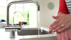 Slow Motion Sequence Of Woman Washing Hands In Kitchen Sink stock footage