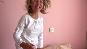 Slow Motion Sequence Of Young Girl Jumping On Her Bed Stock Images