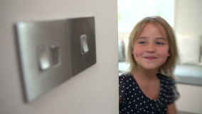 Slow Motion Sequence Of Young Girl Turning Off Light Switch. Slow motion sequence as girl turns off ligh switch and then walks out of frame.Shot on Sony FS700 in stock video