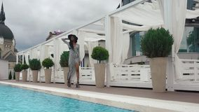 Slow-motion. elegant african american female model in cocktail striped dress and black hat walks at the luxury pool