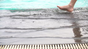 Slow motion shoot of feet walking by pool . Little child walking near swimming pool stock footage