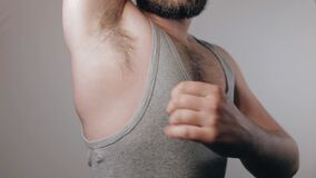 Slow motion shoot of strong man rising his arms, showing biceps and hairy armpits and pounding his chest.