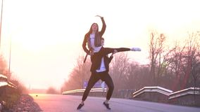 Slow motion shooting as a beautiful couple is dancing and making support in the air against the background of the. A pair of dancers dancing on the road against stock video