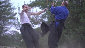 Slow motion shooting as two Japanese warriors fight in the woods and one pushes the other back with a blow to the chest. Deadly battle of two samurai in the stock video