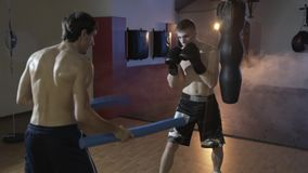 Slow-motion shooting cropped frame, the boxer trains with his coach, fulfills the speed and accuracy of the impact. Boxing, training of sportsmen against the stock video