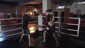 Slow-motion shooting fight club. Boxers train before the fight in the ring. The trainer in boxing paws and a young stock footage