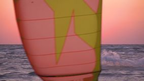 The man controls a bright training kite floating in the sea at dawn. Slow-motion shooting, a man in a diving suit, controls a training kite at dawn stock video footage