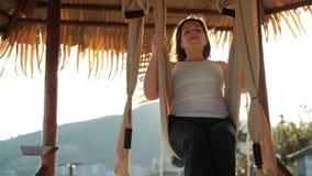 Slow-motion shooting swinging woman on tissue beige swing on shore stock video