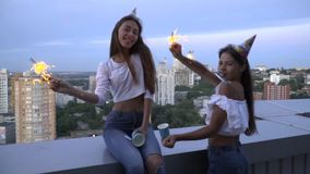 Slow motion shooting of two happy brunette blowing whistles in bright caps and celebrate Happy birthday on the roof of stock video footage
