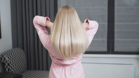 Slow motion shooting of young woman demonstrates long blonde hair
