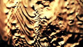 Abstract water drops and streams moving on the glass. Slow motion shot of abstract water drops and streams on the glass, warm colors stock video footage