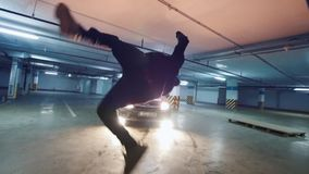 Slow-motion shot of acrobatic guy performs tricks at underground parking. Wide angle stock video footage