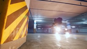Slow-motion shot of acrobatic guy performs tricks at underground parking. Wide angle stock footage
