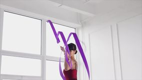 Woman dancing with ribbon. Slow motion shot of beautiful young woman dancing with ribbon. Rhythmic gymnastics performance stock video footage