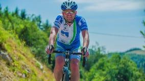 Slow motion shot of a biker racing in marathon, cycling uphill