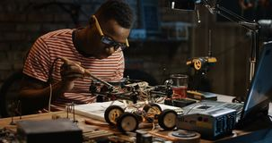 Man repairing a drone. Slow motion shot of a black man repairing a drone in a garage stock video
