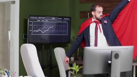 Slow motion shot of businessman wearing a red cape walking silly in the office. Conceptual footage stock footage