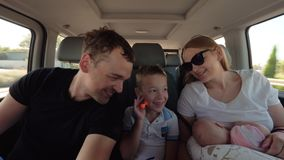 Happy parents with elder son and baby daughter having car journey stock video