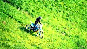 Cross motorcycle moving downhill on the grass hill. Slow motion shot of cross motorcycle moving downhill on the grass hill stock footage