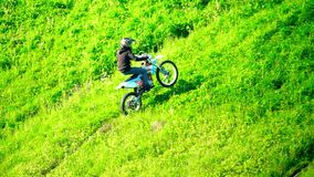 Cross motorcycle moving uphill on the grass hill. Slow motion shot of cross motorcycle moving uphill on the grass hill stock video footage