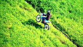 Cross motorcycle moving uphill on the grass hill. Slow motion shot of cross motorcycle moving uphill on the grass hill stock footage