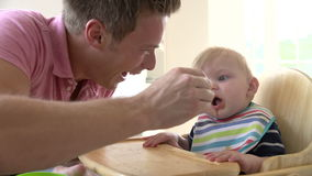 Slow Motion Shot Of Father Feeding Baby Boy In High Chair Stock Photos