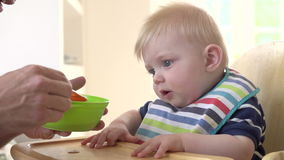 Slow Motion Shot Of Father Feeding Baby Boy In High Chair Stock Photo