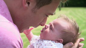 Slow Motion Shot Of Father Holding Baby Daughter In Garden Stock Photos