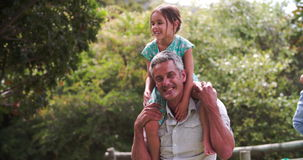 Slow Motion Shot Of Fathers Giving Children Piggyback Rides stock footage