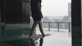 Legs of young woman. Slow motion shot of female feet walking on the bottom of a pool. Water splashes stock footage