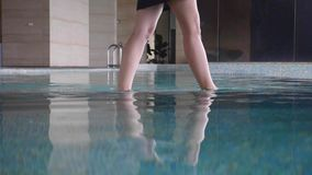 Legs of young woman. Slow motion shot of female feet walking on the bottom of a pool. Water splashes stock video