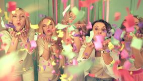 Slow motion shot of five women blowing confetti to the camera at the party. Slow motion shot of five women blowing confetti to the camera. Concept of funny stock footage