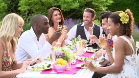 Slow Motion Shot Of Friends Enjoying Outdoor Dinner Party Royalty Free Stock Photo