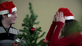 Slow motion shot of guy putting Santa hat on girls head while decorating tree stock footage