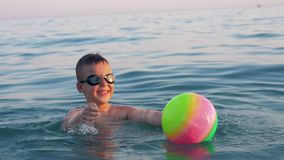 Child playing with ball when bathing in the sea on vacation. Slow motion shot of a happy boy in goggles swimming in the sea and having fun with ball. Water stock video