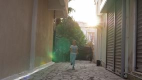 Happy child running in the street. Slow motion shot of a happy and excited boy running along the paved alleyway. Shot with sun flare stock footage