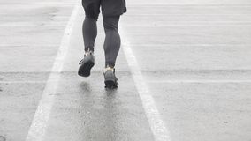 Slow motion shot of legs of a runner in sneakers. Male sports man jogging outdoors. Single runner running in rainy