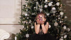 Little girl blowing confetti at Christmas. Slow motion shot of a little girl blowing colorful confetti during Christmas celebration stock footage