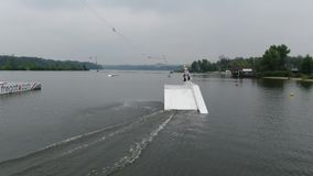 Aerial footage of a wakeboarder jumping on a ramp and spinning around, tricks stock video