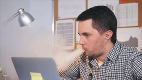 Slow motion shot of man smoking an electronic cigarette in his office. He looks at the laptop monitor. He looks at the screen of a laptop monitor and is stock footage