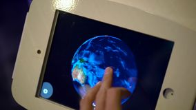 Slow Motion shot of a man that touches a tablet and orbits the model of an Earth. Astronomy exposition.  stock video