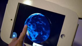 Slow Motion shot of a man that touches a tablet and orbits the model of an Earth. Astronomy exposition.  stock footage